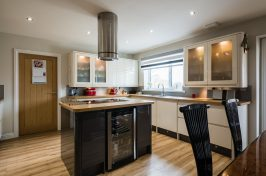 A modern domestic kitchen with high gloss units, rounded corners and an island