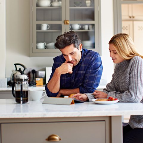 Two people in a kitchen reading documents